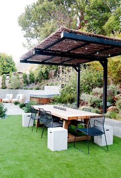 Long wooden outdoor table with black chairs and beige chandelier