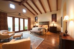 Large modern master bedroom with vaulted ceiling with exposed beams, hard wood floor and sitting area
