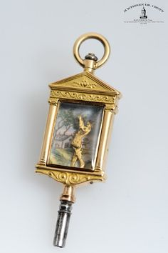 """An exceptional and extremely rare watch key with automaton """"Pulcinella"""" Case: gold and polychrome enamel. Constructional theatre stage, Empire-style columns and pediment; articulated Punch figure (moved by a tiny lever at the back), background with enamelled countryside scene with a farmhouse at a river. Enamelled back, painting of a red open stage curtain and the weapons of Cupid, bow and arrow, in the centre."""
