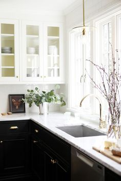 Beautiful Cottage Kitchen Design Remodel. Black lower Cabinets with white upper cabinets and marble counter tops. Gold cabinet pulls, faucet and gold fixtures.