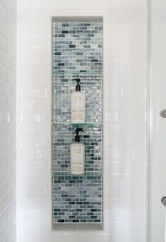 large shower niche with glass tiles and glass shelves. Blue glass shower inset with white subway tile surround #GlassShelves