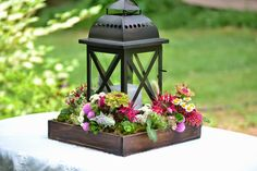 this is quite pretty - a lantern sitting inside a low wooden box (easily made - could even stain the lid of a cardboard box!) and filled with autumn filler.