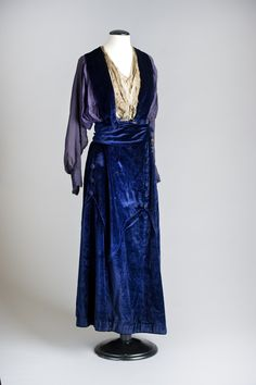 1st WW Afternoon Dress: Ankle-length, in dark blue silk velvet. With a v-neckline, an inset of cream silk chiffon, a shawl collar of blue velvet, an overbodice of dark blue silk chiffon, long magyar sleeves of dark blue chiffon with tight cuffs, a velvet waistband and wide flaring skirt of blue velvet. Trimmed with blue and cream braid on bodice inset, blue embroidery on cuffs, blue tassels on waistband, self-covered buttons and piping on dagged hip yoke. Fastened with hooks, eyes and loops.