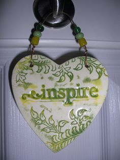 This one of a kind wall hanging was hand cut and stamped with a leafy floral design and the word inspire, fired in my kiln, then glazed using a happy shade of yellow and a nice green to compliment.