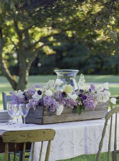 Fill the crate with large jars or plastic containers of water. Place a large hurricane in the center. Add the lilacs and anything else that is growing in the garden like Pansies, Tulips or flowering branches.