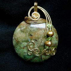 "DARING is a 115 carat handcrafted wire wrapped Pakistani agate pendant that I created swirling and shaping non-tarnish sterling silver plate gold toned wire by hand, adding peridot chips and golden fresh water pearls to enhance the natural beauty and shape of the stone. The olive green and golden tones in this glass-like gemstone display a beautiful earthy and dramatic pendant.   It measures 1 3/4"" across and 2"" top to tip including the bail."