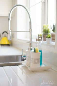 Great idea!  Use bathroom accessories and an oil drizzler to keep the kitchen sink looking tidy and pretty!