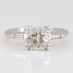 Vintage 1.68 CTW diamond platinum ring with a center European cut diamond at 1.50 carats VVS2 clarity M color and two side baguettes at 0.18 CTW.
