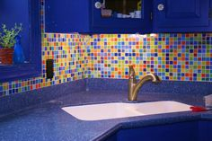Colorful glass mosaic in a blue kitchen by Susan Jablon