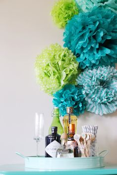 A festive backdrop made with DIY tissue paper pom poms from The Sweetest Occasion