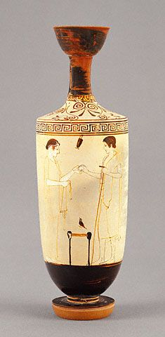 Oil Jar with an Egg Offering (Getty Museum). Greek, Athens, 460 - 450 B.C.A young woman and a youth face each other over a low stool on this Athenian white-ground lekythos. The youth hands the woman an egg, which functions in Greek art as both a love gift and a symbol of rebirth. The scene surely depicts a family preparing for a funeral, since the woman holds a fillet or wide ribbon in her hand. Long fillets were tied around tombstones as a part of funerary ritual.
