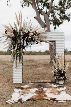 iron wedding arch with plumes of pampas grass and burgundy flowers
