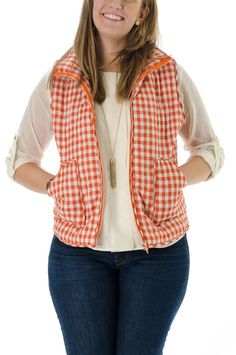 A layering essential, this orange gingham puffer vest features all-over quilting, front zipper closure and side pockets. Layer this vest over your favorite button-up!