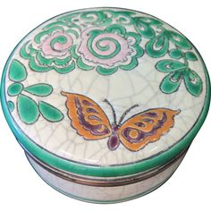 Early 20th century French pottery trinket box is designed  produced by Longwy. The box is decorated with an enamel green  pink floral pattern