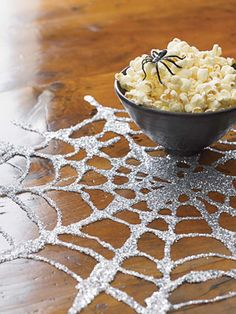 Elmer's Glue on wax paper + glitter. Once dried, peel off for nifty spiderwebs!  center of table`, hang in windows