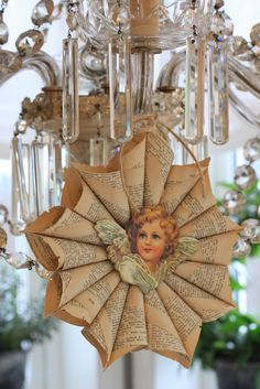 "To do this:  Roll the cones of the pages from the book and paste form a ""ring"" as the asterisk (Tips of the cone houses are  stitched together with needle and thread)  An angel in cardboard covers the seams."