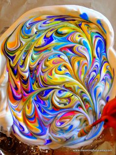 Use drops of food coloring, on shaving cream.  Swirl (gently to still keep colors vibrant).  Carefully lift the paper up. Using a straight edge (We used a dish scraper), scrape of the shaving cream. Revealed underneath will be gorgeous marbled paper. Allow to dry.