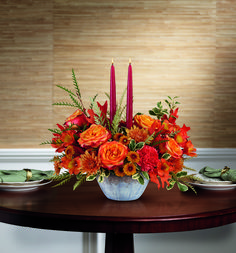 Transform your #tablescape this #fall! This lush autumnal rose #centerpiece is arranged in a stunning, oven-to-table ceramic serving bowl with gorgeous artisanal glaze in steel blue hues. Orange bi-color roses, orange alstroemeria, orange #carnations, orange button spray #chrysanthemums and rust cushion spray chrysanthemums are accented with grevillea, oregonia, and two dark burgundy candles. Delivered in Teleflora's Bountiful Blessings Bowl. Starting at $69.99
