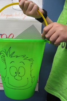 Draw a happy face on a plastic sand bucket for a fun Bucket Filler visual!
