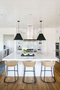 BECKI OWENS- Estillo Project: Classic Modern Kitchen. A white kitchen with statuary marble, Benjamin Moore Swiss Coffee paint, black cone pendants, and rattan counter stools.