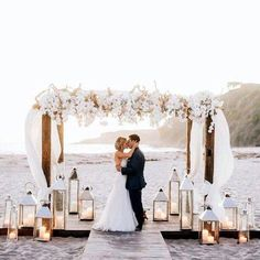 This is absolutely beautiful! Love the risers in the sand with candle lit lanterns on the beach. The lanterns and flowers give this a romantic and elegant feel. #alexalcalire #beachwedding #weddingideas #weddinginspiration