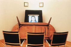 Adrian Piper, Cornered, 1988. Single-channel video installation with monitor, overturned table, ten chairs, and framed photocop- ies of two birth certificates for Piper's father. Museum of Con- temporary Art, Chicago, Bernice and Kenneth Newberger Fund