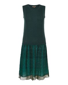 The top is a soft, stretchy sleeveless sweater in deep forest green with a textured front and ribbed crew neckline. Attached is a fun and feminine chiffon skirt in print lined by a cotton skirt underneath. Together, this all-in-one outfit gives you a perfectly paired complete look in one easy piece.