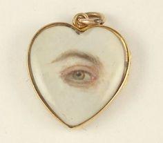 """lovers' eye"", eye miniature on ivory, c. 1830s. hand-painted miniature of a left hazel eye on ivory in heart-shaped pendant."