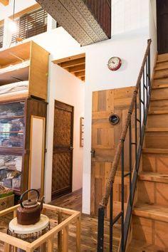 寄せ木にレンズの明かり窓をつけたドアはKINTAさん作。奥は飛騨高山の骨董屋で見つけたもの。階段の手すりもKINTAさん作。
