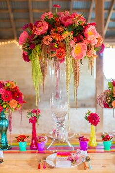 Loud and vibrant color palettes are so fun for a fiesta wedding. Full of bright, juicy hues, the colors work perfectly during summertime as seen in this hanging flower arrangement surrounded by colorful vases.
