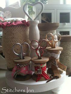 Utiliza unas bobinas de madera y decóralas con puntillas, cintas y charms. Las puedes emplear para colocar tus tijeras y así encontrarlas rapidamente.