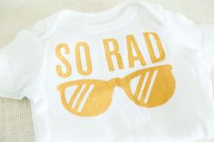 So Rad baby bodysuit by FMC studio. Screen printed by hand in metallic gold ink. Available in sizes 3-9 months.