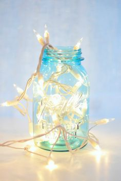 "Christmas lights in a blue Mason jar....on one of the deep window sills with red bakers twine going in front to form a ""rail"""