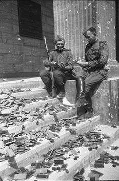 Soviet soldiers resting on the steps of the Reich Chancellery looking at German medals that have not been awarded, nor will they be, photographed by Yevgeniy Khaldei (Berlin May 1945)