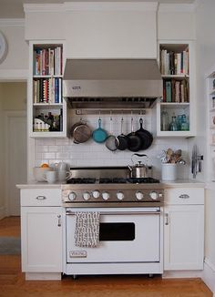 book shelves in kitchen.. I like the pans hanging over the stove idea the best!