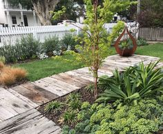 Recycled timber path contains a central feature with athe addition of a corten steel feature planter.