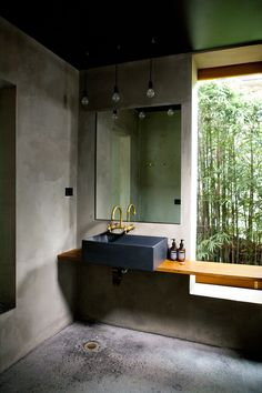 13 Ideas For Creating A More Manly, Masculine Bathroom // Anything industrial is a surefire way to make the bathroom more masculine. Here, a black sink, concrete walls and floor, and brass combine to create an industrial and masculine feeling bathroom.