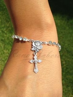 "This exclusive bracelet is handmade using genuine Swarovski® rhinestones along with a silver rose connector and silver crucifix. Findings are plated silver. Measures approximately 7"" with a 1.5"" exten"