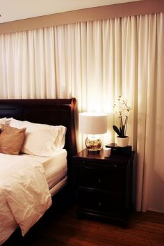 Master bedroom makeover. White bedding. Greige walls, sleigh bed, wall of fabric curtains covering odd window.