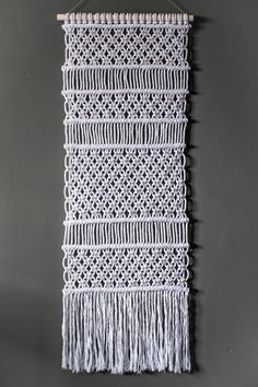 This handmade macrame wall hanging is made using recycled cotton cord in white with a pine dowel which has been sanded and painted white.