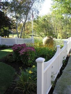 The picket fence is the one we associate with small-town America and our colonial roots.  It's the fence most at home in front of Cape Cod and colonial-style homes.  Because a picket fence isn't meant to be tall and visually opaque, it's more often than not used to define an edge or a corner as well as to create a backdrop. As such, a picket fence is more appropriate for a front yard, where it can enhance curb appeal, forming the backdrop for all those wonderful summertime blooms. Landscaping Around Trees, Backyard Fences, Fenced In Yard, Front Yard Landscaping, Landscaping Ideas, Courtyard Landscaping, Garden Fences, Yard Fencing, Rain Garden
