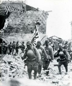 Japanese troops marching through the rubble of a village near Hankow.