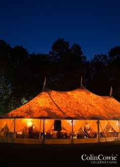 After the sun has set, a leaf pattern projected onto the roof of the tent adds warm light to the reception.
