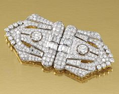 DIAMOND DOUBLE CLIP BROOCH, 1930S.  Of odeonesque design, each open work shield-shaped clip set with circular-cut and baguette diamonds, detachable brooch pin, fitted case.