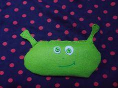 Décembre 2013. Tissus, boutons, lentilles, fil, feutrine... Peluche repose-yeux en forme de Shrek-alien. Réalisée comme cadeau de Noël pour Bestiole.