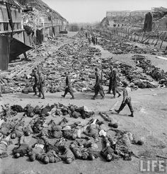 American soldiers  walking past rows and rows of corpses  at the Nordhausen concentration camp just after its liberation.  Location: Nordhausen, Germany   Date taken: April 1945