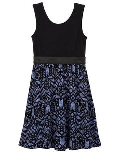 A sleeveless dress featuring a black bodic, and a flowing skirt with a blue and black geo print design.