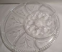 This Deviled Egg and Relish Tray is crystal clear and manufactured by Indiana Glass Company. It features the Tree of Life pattern. There is space for 8 deviled eggs surrounded by seven separate divided areas. It is in excellent condition with no chips, cracks, or nicks. It weighs 4.5 pounds and is a nice size of 12 3/4 in diameter. Please see all my vintage serving pieces at https://www.etsy.com/shop/DeliciasCastle?section_id=12369758&ref=shopsection_lef...