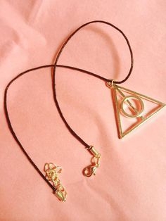 The choker is made personally by myself. It consists of a black cord choker (1mm) with a large enamel Deathly Hallows Charm in the center. The