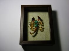 Turquoise and amber glass scorpion, with a few wooden beads in there, too. Neat gold crackle print cotton background, $40.00 UPDATE: sent to a gift shop in Sedona, AZ called Scorpion on the Porch, to sell.